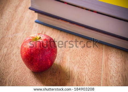 Book and red apple on wood - stock photo