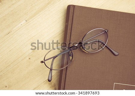 Book and Spectacles on a wooden table