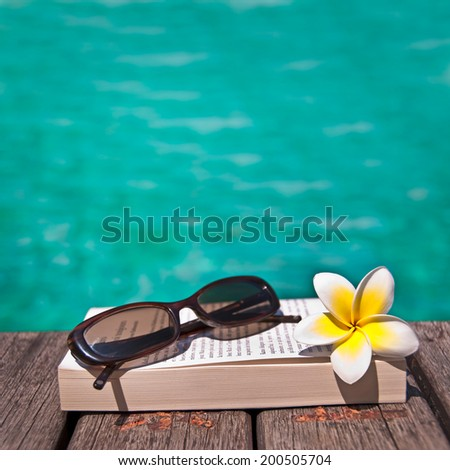 Book and sunglasses, blue water, background - stock photo