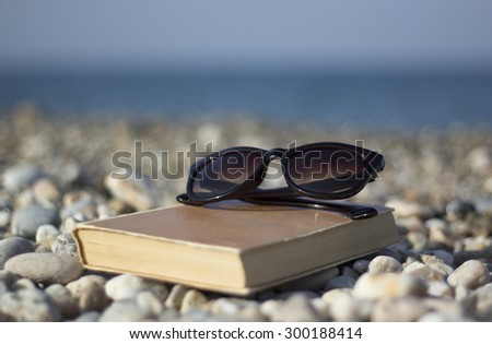 Book and sunglasses on the beach. Shallow depth of field. - stock photo