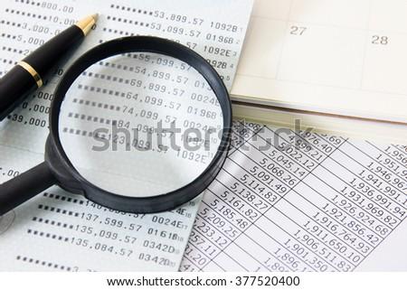 Book bank, Magnifier, Calendar, a ball pen. - stock photo