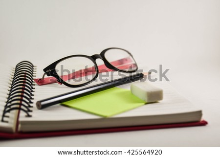 Book binding with pencil and Spectacles on white background