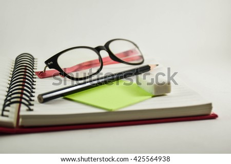 Book binding with pencil Eraser  and Spectacles on white background