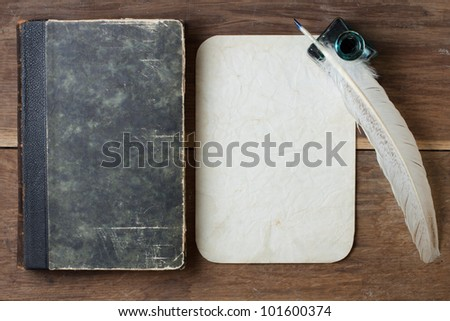 Book cover, quill and inkwell, old grunge paper on wood background - stock photo