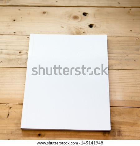book cover white on wood table - stock photo