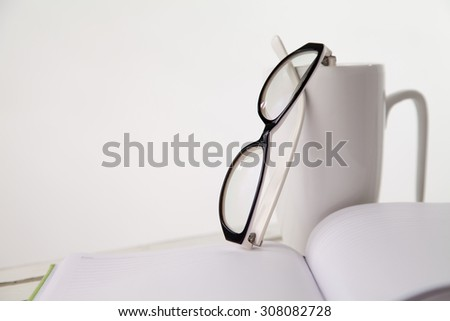 Book,glasses and cup on the table in white background - stock photo