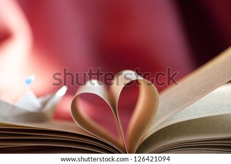 Book heart and a paper boat. Romantic trip concept. - stock photo