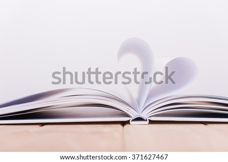 Book heart on wood floor and white background