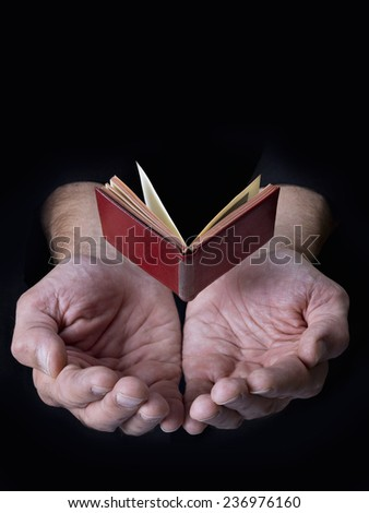 Book in the air with hands below - stock photo