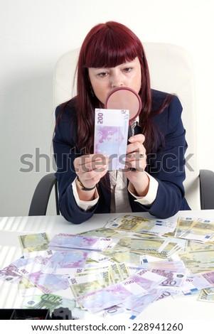 book-keeper with loupe checks 500 euros - stock photo