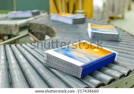 Book, magazine,  production line into press plant house. Automatic assembly line. - stock photo