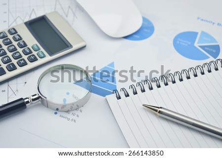 Book, magnifying glass, pen and calculator on financial chart and graph, accounting background - stock photo