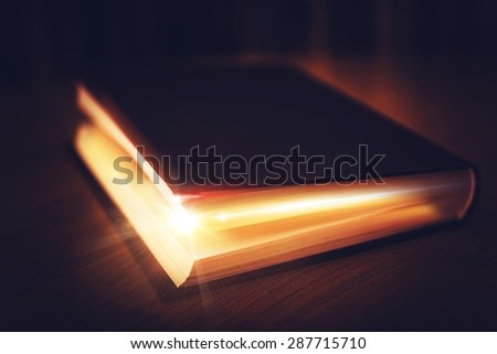 Book of Mysteries. Old Book with Glowing Content. Magical Book. - stock photo