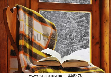 Book on a chair with blanket, in a mountain home with snowfall - stock photo