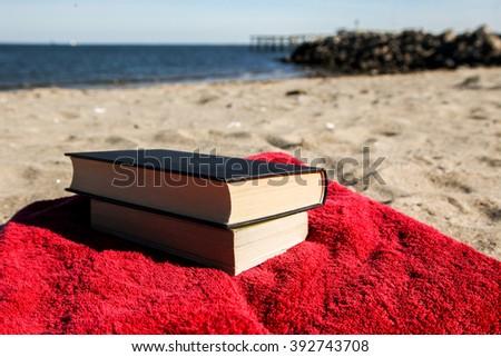 Book on beach with blue sky horizontal - stock photo