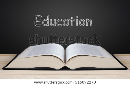 Book on blackboard background and light, education concept