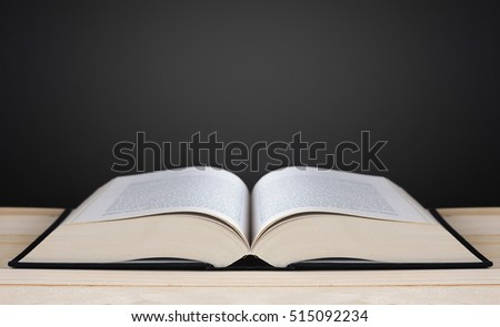Book on blackboard background, copy space and light, education concept