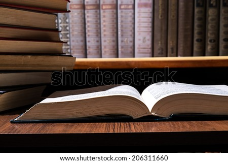 book on the table, the left stack of books against the background of the bookcase