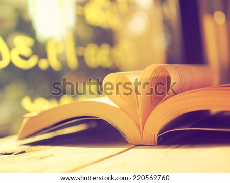 book on the wood desk in vintage color tone style - stock photo