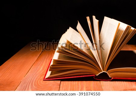 Book opened in library on wooden shelf. Education background with copy space for text - stock photo