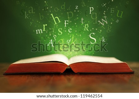 Book or bible on table with flying letters on green background