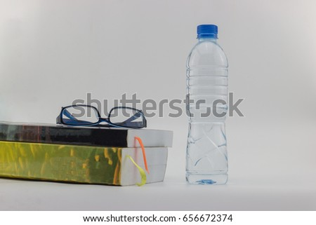 Book packs and glasses placed next to bottles of drinking water. On a white background