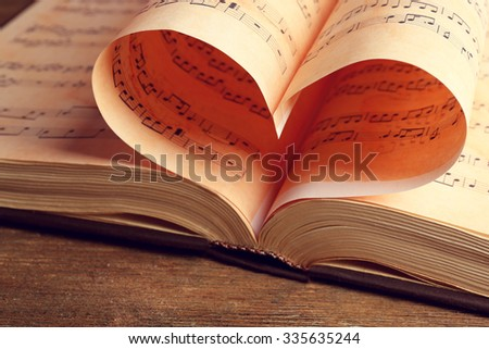 Book pages curved into heart shape close up