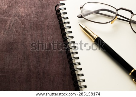 book pen and glasses on wooden table with space for your text - stock photo