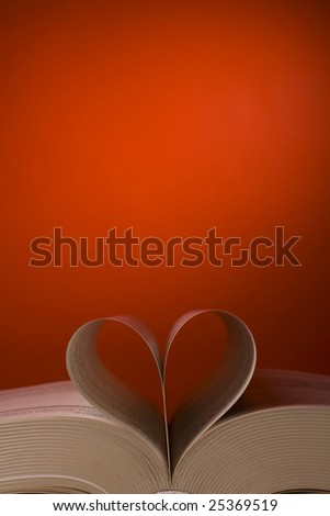 Book's pages in heart and swans form is on the red - stock photo