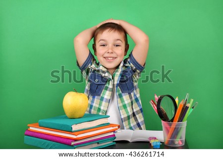 Book, school, kid. School boy at the classroom working at the table. Photo of teen, creative concept with Back to school theme. A child of primary school age do homework. Adorable child studying. - stock photo