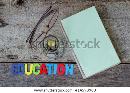 Book, spectacles, a glass of jar filled with coins and colourful word EDUCATION on wooden table. Concept of saving for education. - stock photo