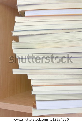 Book stack against book shelf