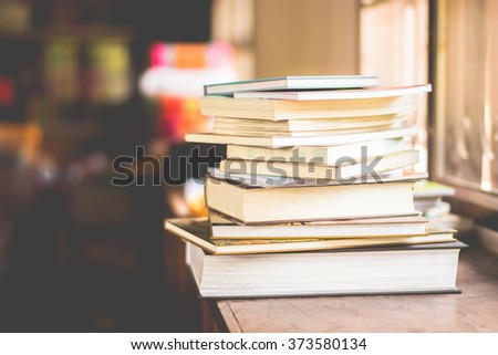 book stack beside window with dark blurred background - stock photo