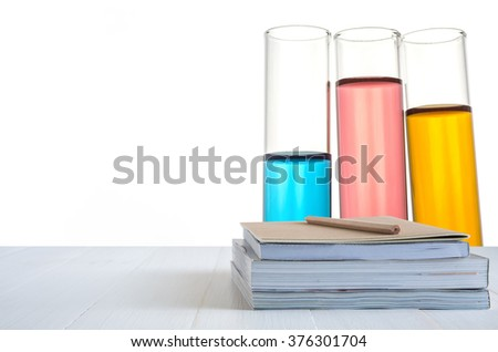 book stack on white table with science laboratory test tubes background - stock photo