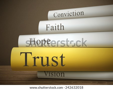 book title of trust isolated on a wooden table over dark background - stock photo