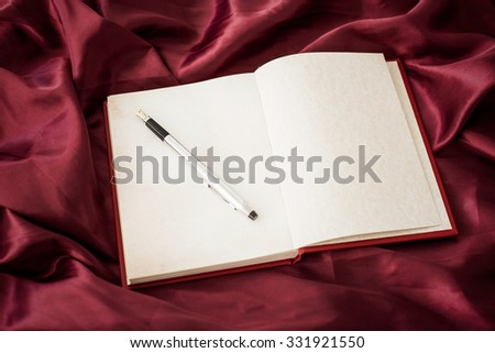 Book with a pen on red satin