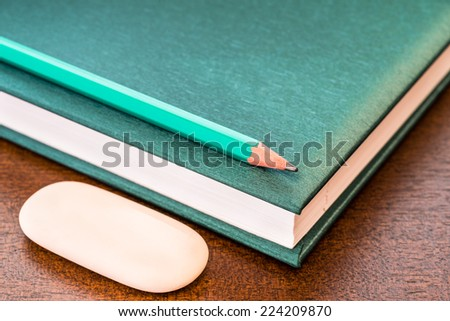 Book with a pencil and eraser on the table - stock photo