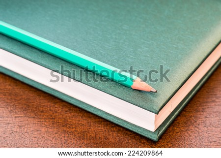 Book with a pencil on the table - stock photo