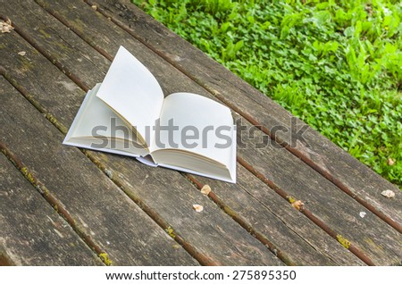 Book with Blank Pages lying open on a Wooden Table Outdoor - stock photo
