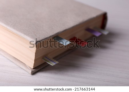 Book with bookmarks on wooden background - stock photo