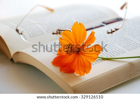book with glasses and cosmos flower