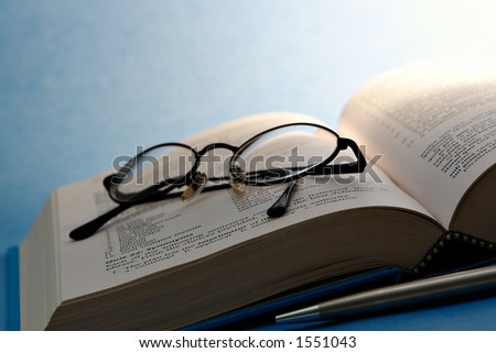 Book with glasses and pen