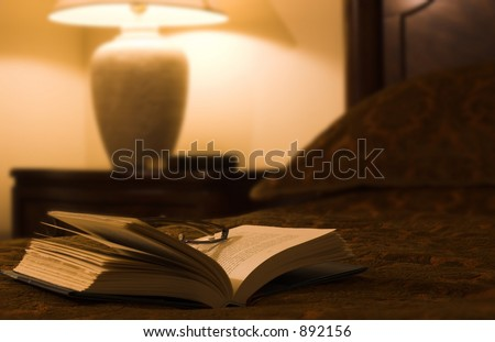 book with glasses on a bed - stock photo
