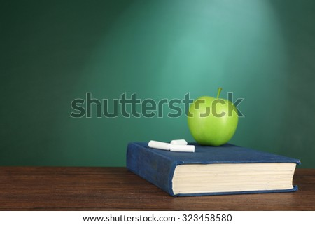 Book with green apple and pieces of chalk on green chalkboard background