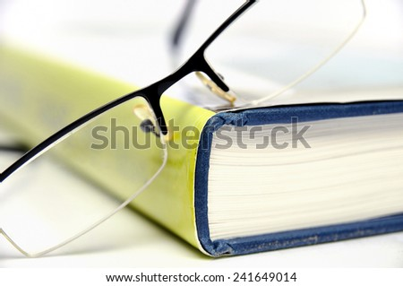 Book with green cover an black glasses - stock photo