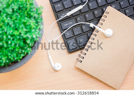 Book with headphones and the keyboard is placed on wooden floor,vintage color tone.