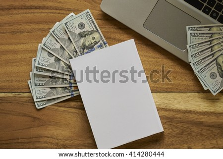 Book with money and laptop top view - stock photo