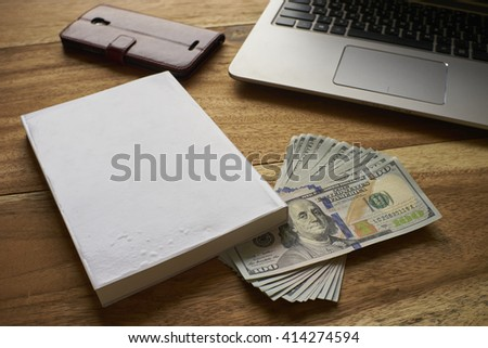 Book with money laptop and mobile phone - stock photo