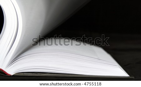 Book with moving sheets on a black background
