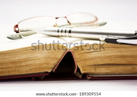 book with pen and glasses - stock photo